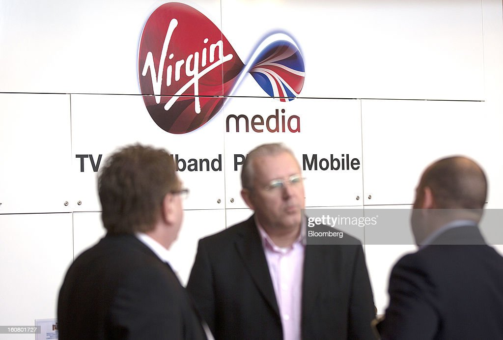 A group of businessmen stand underneath the Virgin Media logo as they wait in the reception area at the company's headquarters on the Bartley Wood Business Park in Hook, U.K., on Wednesday, Feb. 6, 2013. Billionaire John Malone's Liberty Global Inc. agreed to acquire Virgin Media, Britain's second-largest pay-TV provider, in a $16 billion cash-and-stock transaction announced in the U.S. yesterday. Photographer: Simon Dawson/Bloomberg via Getty Images