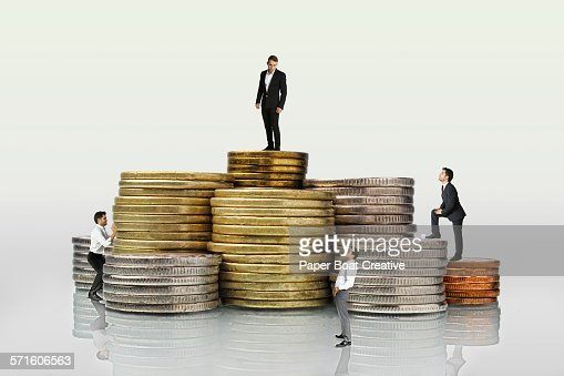 Group of businessmen standing on different coins : Stock Photo