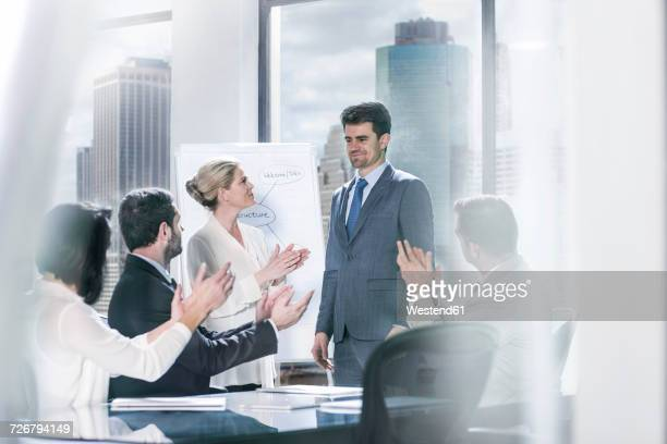 Group of businesspeople clapping hands after a presentation in city office