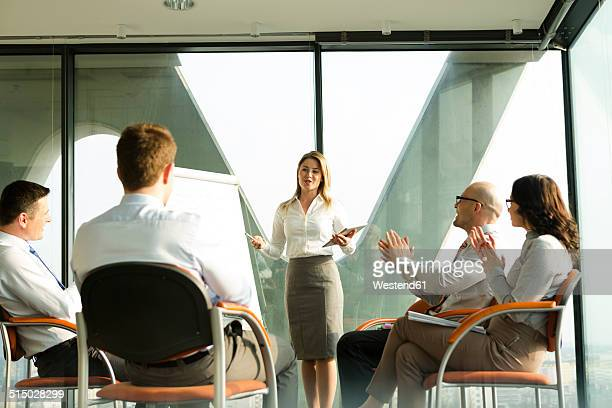 Group of businesspeople clapping hands for businesswoman at flip chart