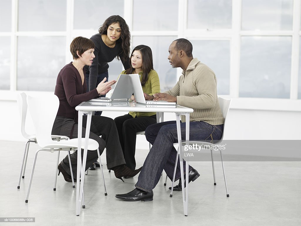 Group of businesspeople discussing with laptop : Stock Photo