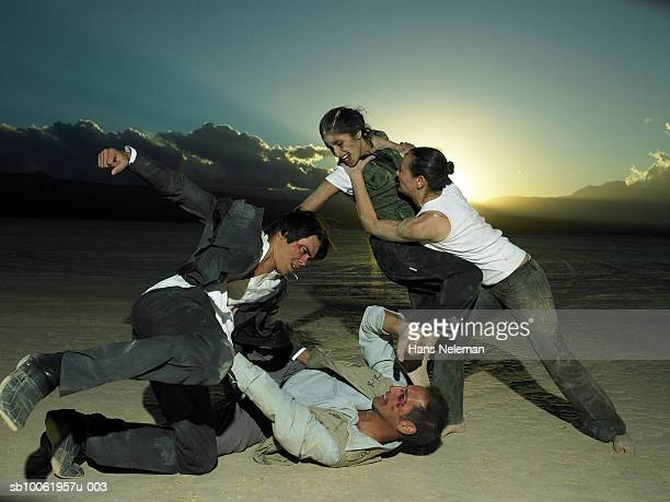 Group of businesspeople fighting in desert at dusk
