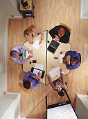 Group of businesspeople having business meeting in office, overhead view