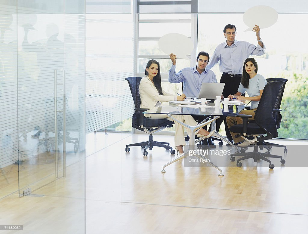 Group of businesspeople in boardroom with speech balloons : Stock Photo