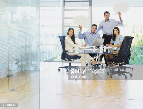 Group of businesspeople in boardroom with speech balloons : Bildbanksbilder