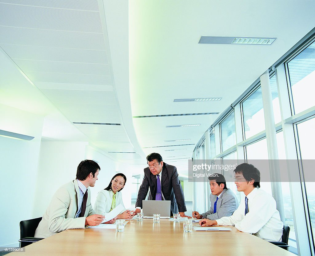 Group of Businesspeople Planning Strategy all Looking at One Man