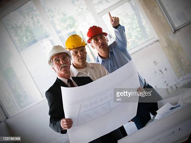 Gruppe von Geschäftsleuten, die Überprüfung Werkzeuge zusammen auf Baustelle