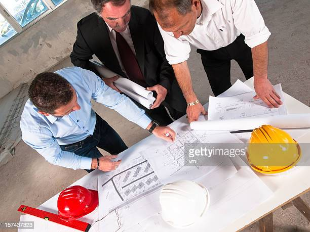 Group of Businesspeople Reviewing Blueprints Together on Construction Site