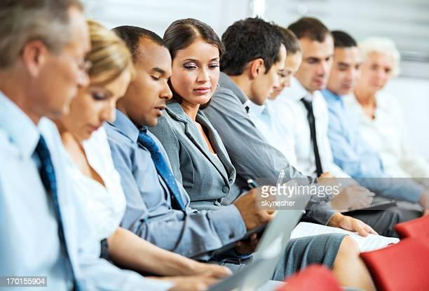 Groupe d'hommes d'affaires assis dans une ligne.
