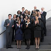 Group of businesspeople standing on outdoor stairs clapping