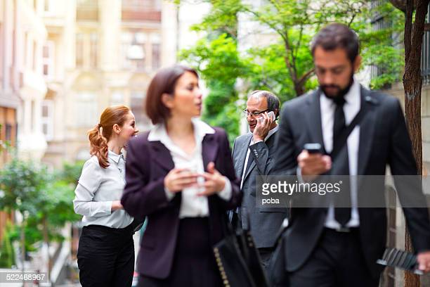 Group Of Businesspeople with mobile phones  walking down the street