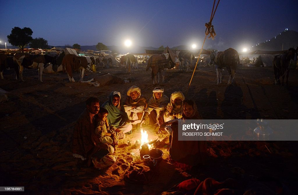A group of camel traders sit around a fire in the early morning hours at the camel fair grounds on the outskirts of Pushkar on November 21, 2012. The annual five-day camel and livestock fair, held in the town of Pushkar in the state of Rajasthan is one of the world's largest camel fairs, and apart from buying and selling of livestock it has become an important tourist attraction. AFP PHOTO/Roberto Schmidt