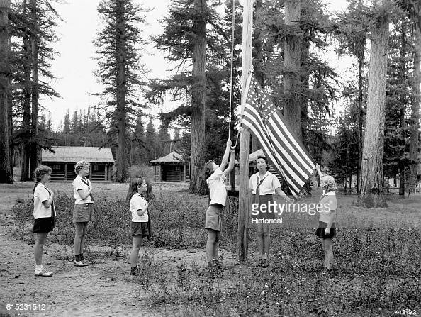 A group of Camp Fire Girls raise the American flag at Camp Paxson in Lolo National Forest Montana 1941 | Location Camp Paxson Seeley Lake Lolo...