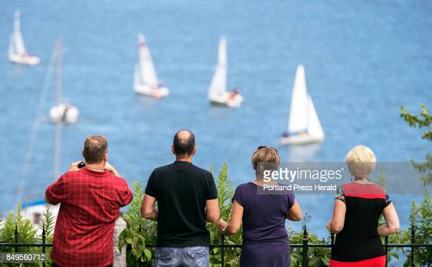 A group of Canadians on a twoweek vacation from the Lac St Jean region of Quebec Province watches a sailing regatta on Casco Bay from Fort Allen Park...