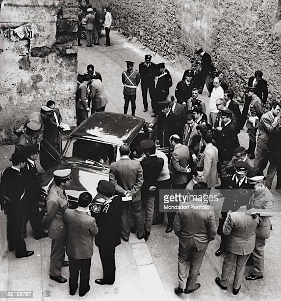 A group of Carabinieri and onlookers looking inside the FIAT 130 the bodies of Chief Prosecutor of Palermo Pietro Scaglione and his driver Antonino...