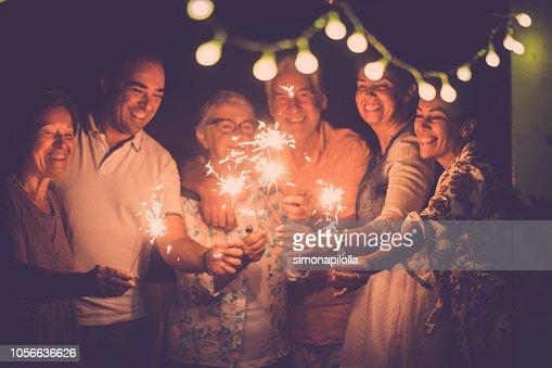 Grupo de amigos de gente caucásica con diferentes edades celebrar juntos un cumpleaños o el año nuevo por la noche al aire libre en casa. luces y destellos con alegres mujeres y hombres que se divierten en la amistad : Foto de stock