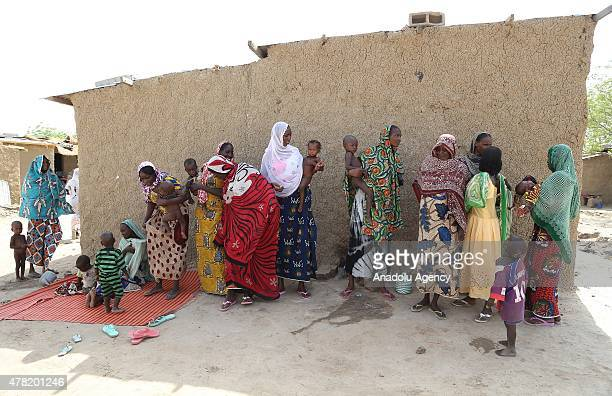 N'DJAMENA CHAD JUNE 22 A group of Chadian women carrying their babies stand next to a house in a village near the capital N'Djamena Chad on June 22...