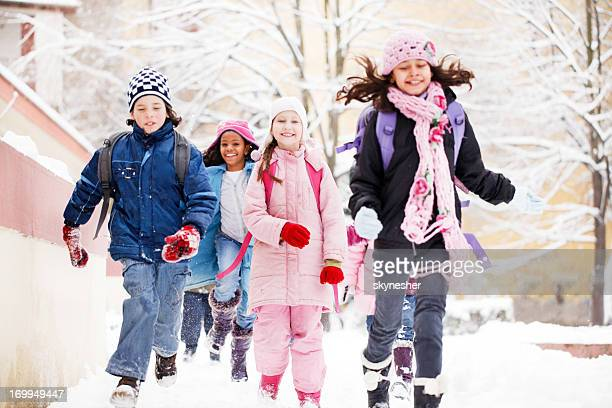 Group of cheerful children running in the snow.