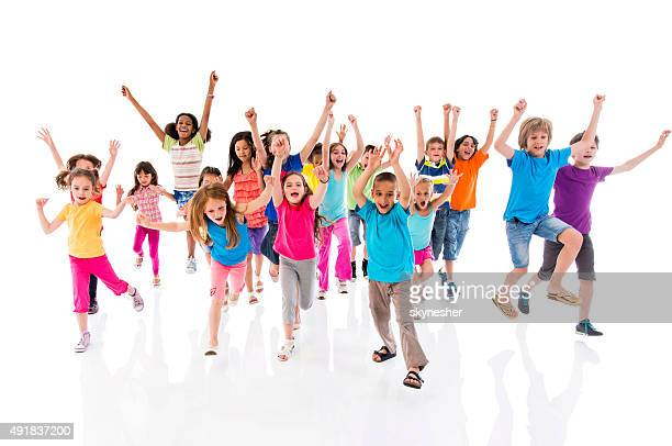 Group of cheerful children running with raised hands.