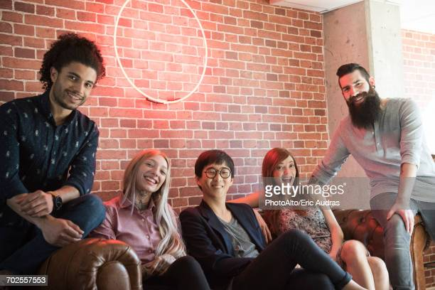 Group of cheerful friends hanging out together on sofa, portrait