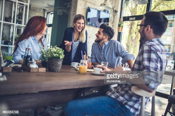 Group of cheerful friends having fun while talking in a cafe.