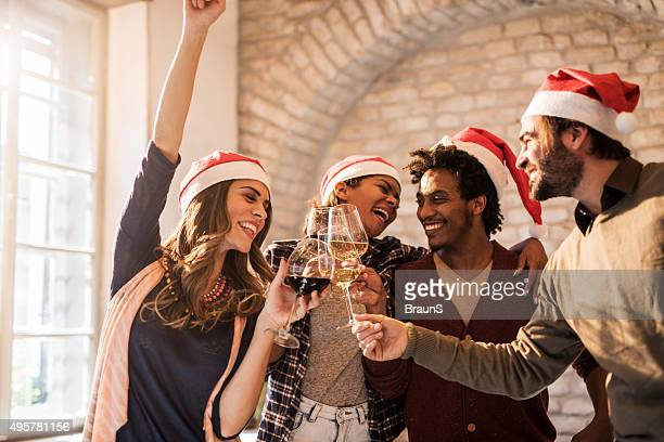Group of cheerful friends toasting to upcoming New Year.