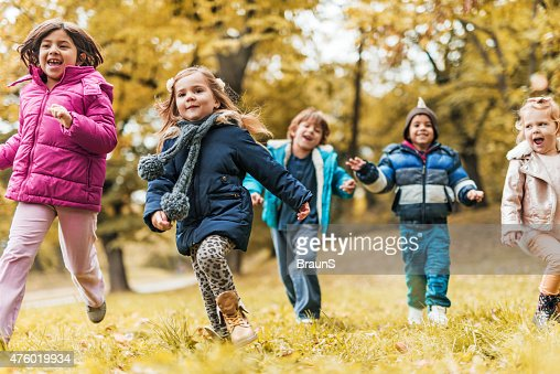 Group of cheerful kids running in nature during autumn day.