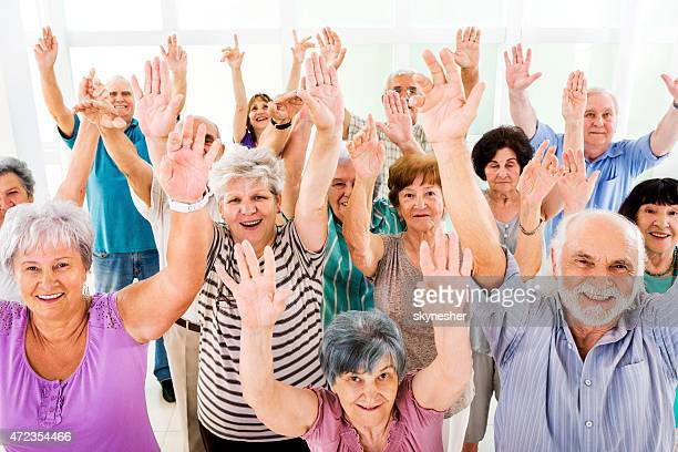 Group of cheerful seniors with raised hands looking at camera.
