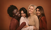 Group of cheerful young women standing together on brown background. Multi ethnic female friends in studio.