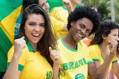 Group of cheering brazilian soccer fans with flag of brazil supporting the national team at stadium