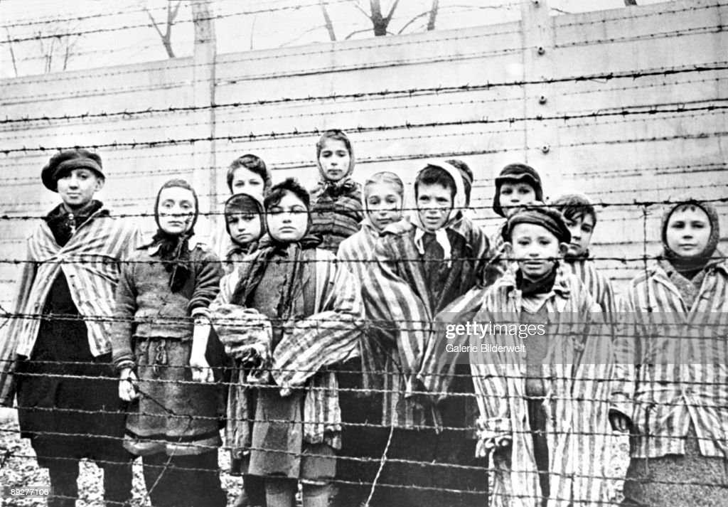 Jewish children, survivors of Auschwitz, behind a barbed wire fence, Poland, February 1945. Photo taken by Russian photographer Alexander Vorontsov during the making of a film about the liberation of the camp. The children were dressed up by the Russians with clothing from adult prisoners.