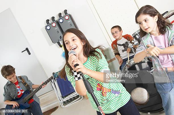 Group of children (7-10) acting as band, playing instruments in garage