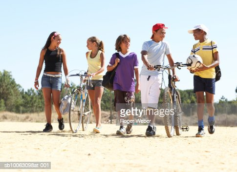 Group of children and teenagers (11-14) walking on beach with bicycles and balls : Foto de stock