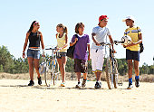 Group of children and teenagers (11-14) walking on beach with bicycles and balls