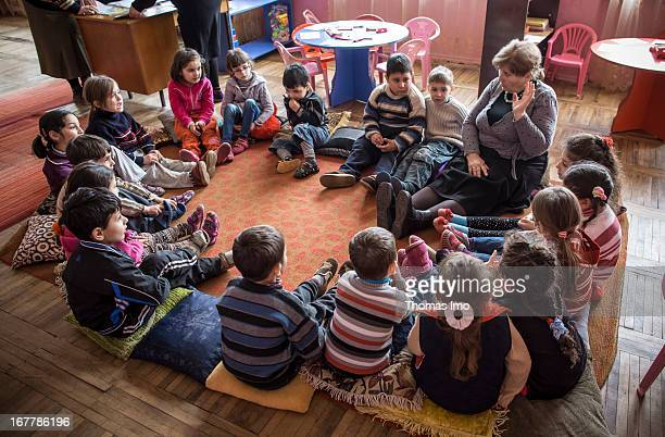A group of children and their teacher sitting in circle on the floor at a kindergarten in Akura Georgia on March 12 2013