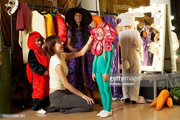 Group of children (5-9) backstage, teacher adjusting girl's flower costume