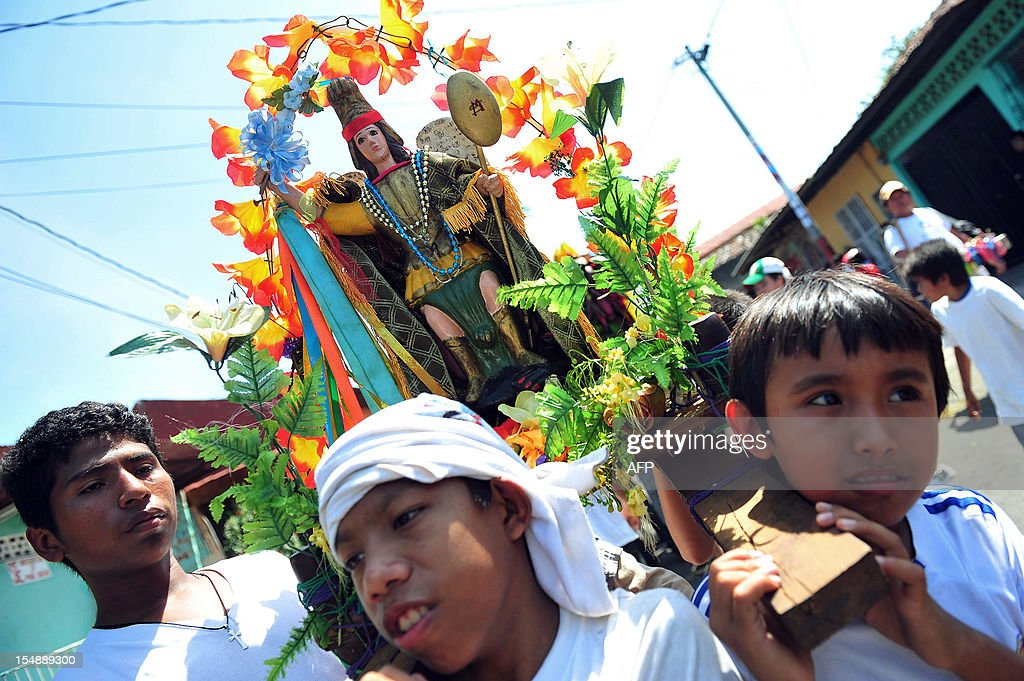 A group of children carry a statue of San Miguel during the 'Torovenado' carnival held in the framework of San Jeronimo celebrations, the patron saint of Masaya, 30 km from Managua, on October 28, 2012. The festivities honouring San Jeronimo - which are known as the longest festivities in Nicaragua - began September 20 and end the last Sunday of November. AFP PHOTO/Hector RETAMAL