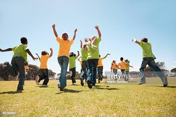 Gruppe von Kindern jubeln und läuft im park