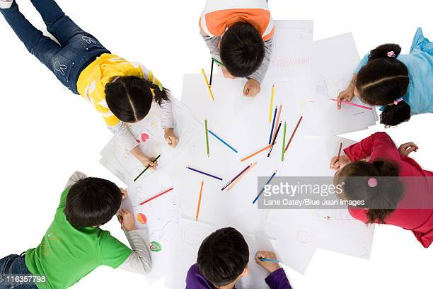 A group of children coloring together on the floor