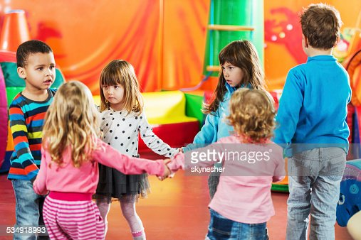 Group of children dancing in a circle.