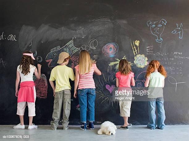 Group of children (7-9 years) drawing on chalkboard, rear view