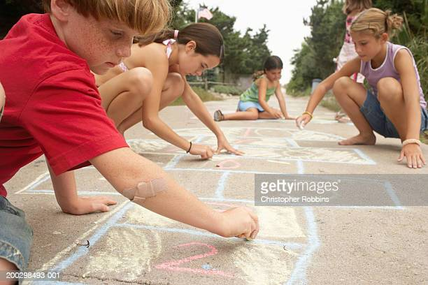 Group of children (7-12) drawing on ground with chalk, close-up