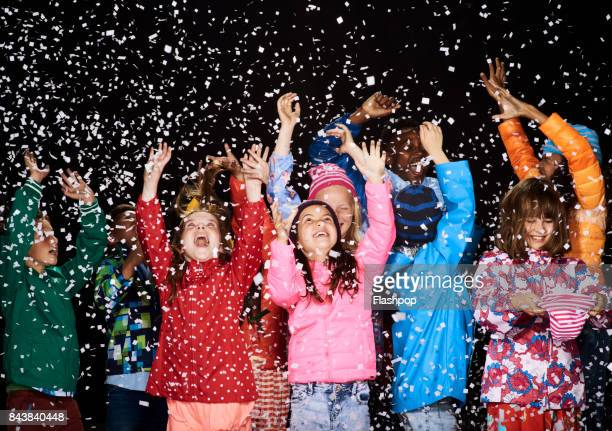 Group of children dressed in winter coats having fun in the snow