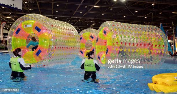 A group of children enjoy rotating on water inside giant inflatable tubes on the first day of the London Boat show 2014 at the ExcCel centre...
