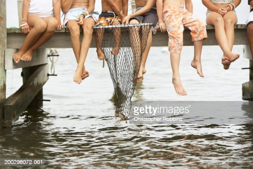 Group of children (3-13) fishing from jetty, low section : Stock Photo
