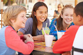 Group Of Children Hanging Out Together In Cafe With Drinks SmilingŽ