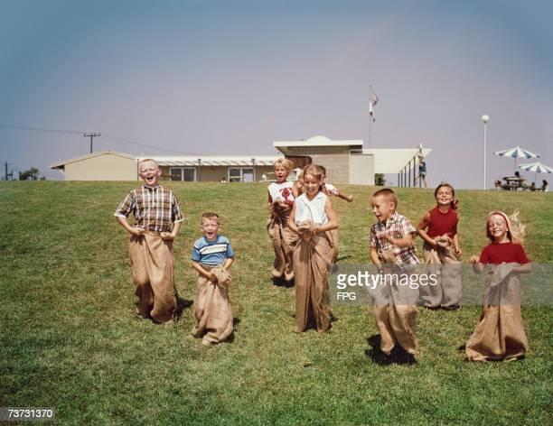 A group of children having a sackrace circa 1960