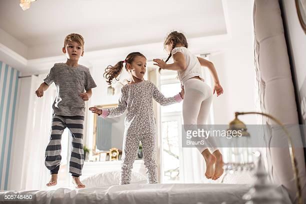 Gruppo di bambini divertirsi mentre saltare su un letto.