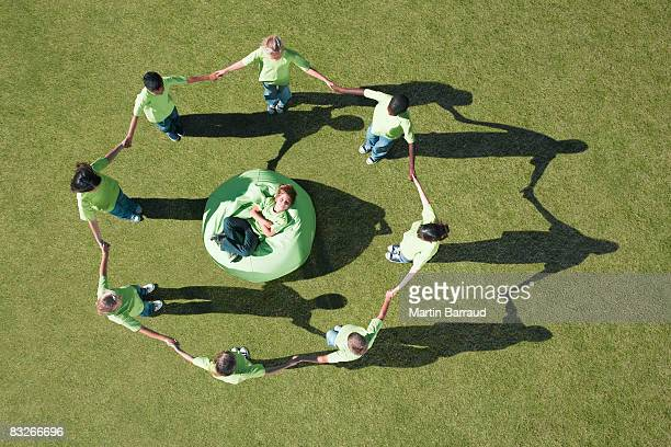 Group of children holding hands around boy in bean bag