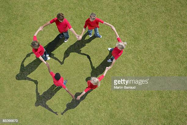 Group of children holding hands in heart-shape formation